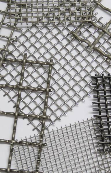 Several different mesh sizes of wire mesh panels on the table.